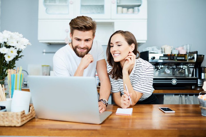 Young man and woman behind the counter of what looks like an eatery or coffee shop and looking at a laptop screen.