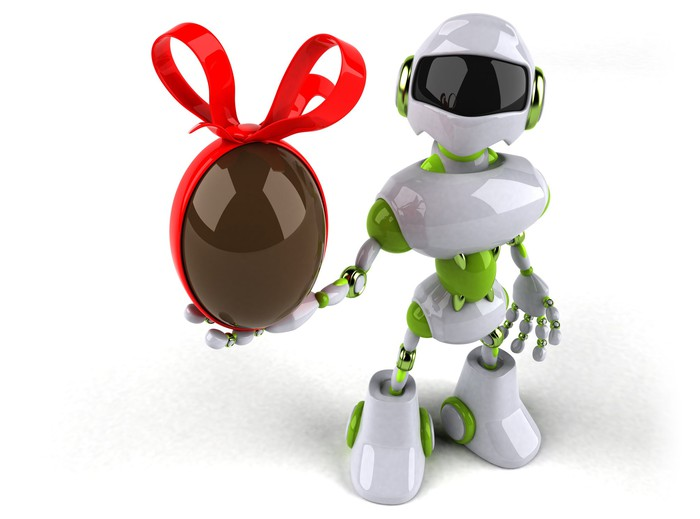 A robot holding a brown Easter egg with a red bow on it.