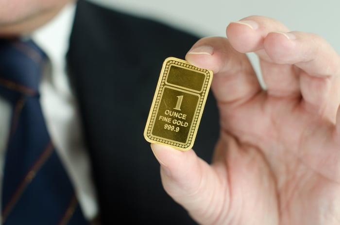 A man holding up a gold ingot