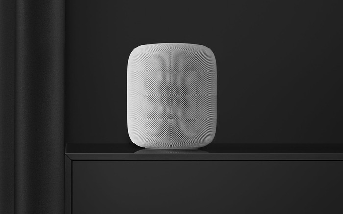 A white Apple HomePod against a dark gray wall and on a dark gray table.