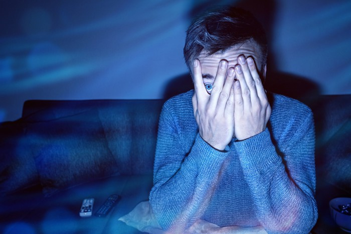 An apparently frightened man peeking through his fingers while watching TV in the dark.