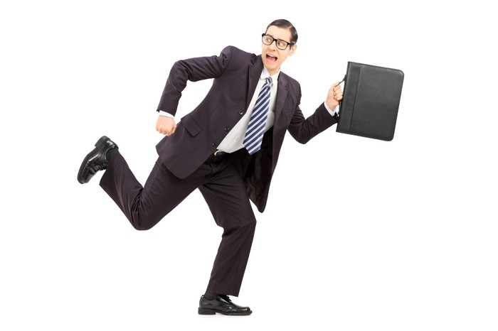A man in a suit carrying a briefcase and running away