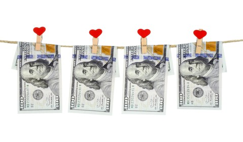 $100 bills hung on  a string by closepins with a heart on them.