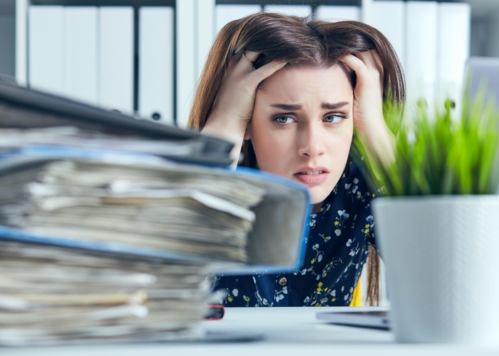 Woman holding her hair with distressed expression while staring at a stack of binders loaded with papers