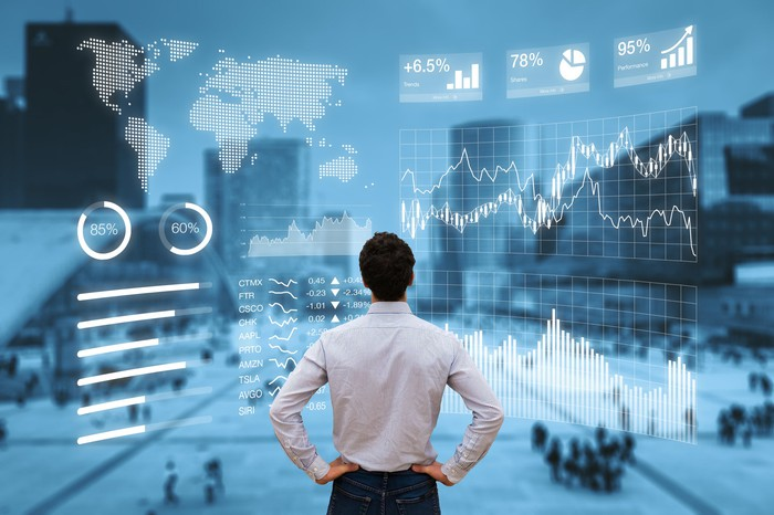 Man looking at city scene with stock graph displays.