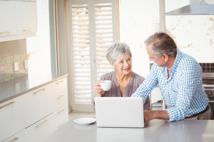 Senior couple at laptop in kitchen; woman is holding a mug and man is typing