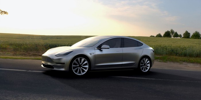 A silver Tesla Model 3 on a road, with a green field in the background.