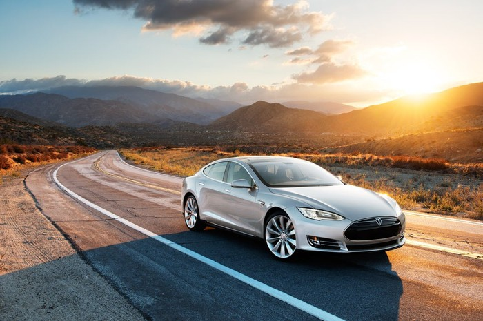 A silver Tesla Model S runs on a road with slopes in the background.