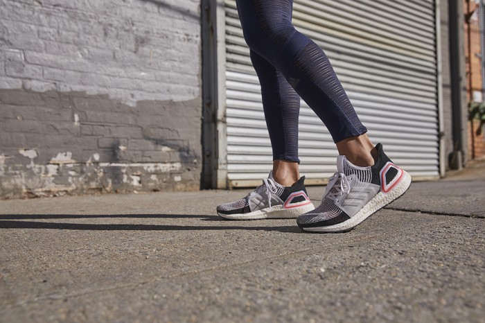A woman wears a pair of Adidas sneakers.