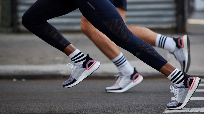 Two runners running in Adidas UltraBoost shoes.