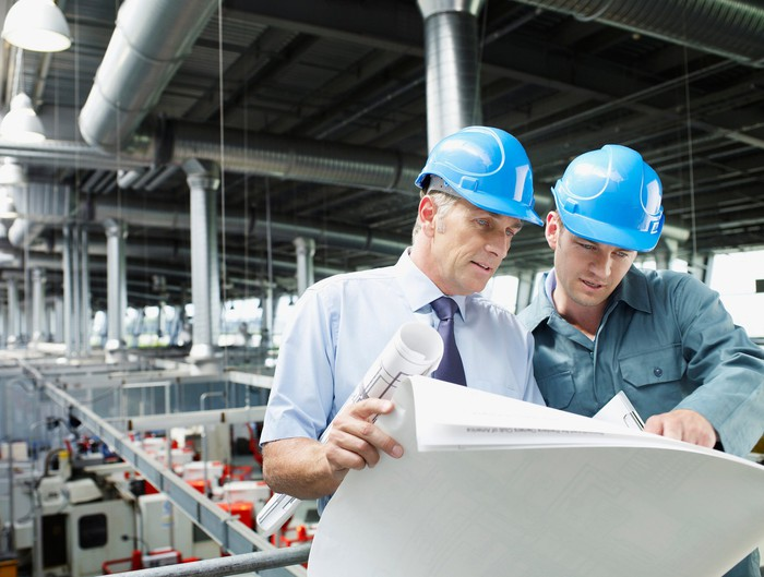 Two men in hard hats looking at blueprints with an industrial work floor behind them