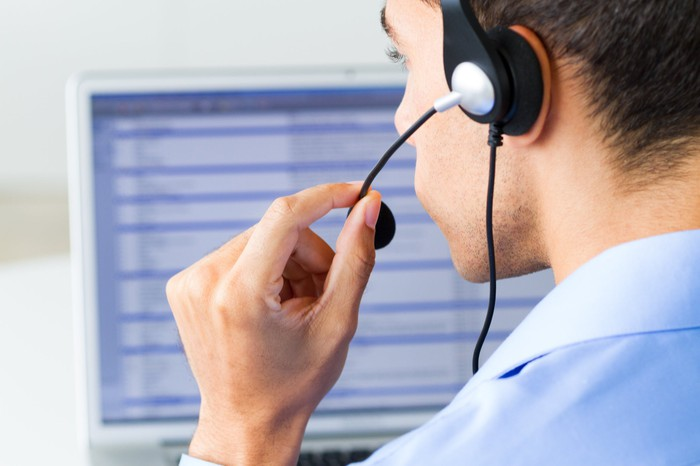 An employee talks into a headset while sitting in front of a computer.