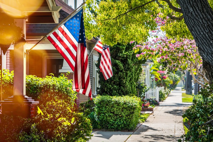 American flags hanging on homes on a tree-lined street.