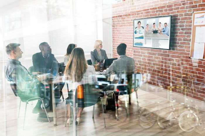 Business team meeting with co-workers in a conference room via video conferencing