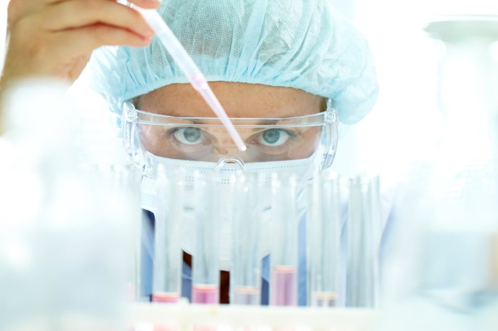 Lab employee pipetting pink liquid into test tubes.