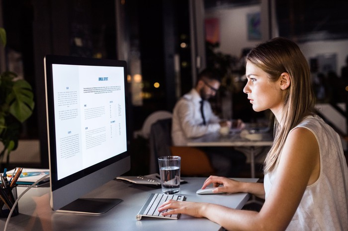 Woman typing on keyboard in front of computer screen in dark office.