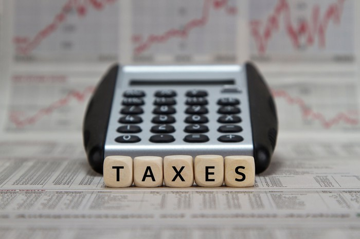 The word taxes spelled out in tiles in front of a calculator