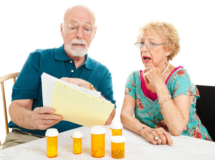 A distraught senior couple looking at a medical bill, with five prescription bottles on the table in front of them.