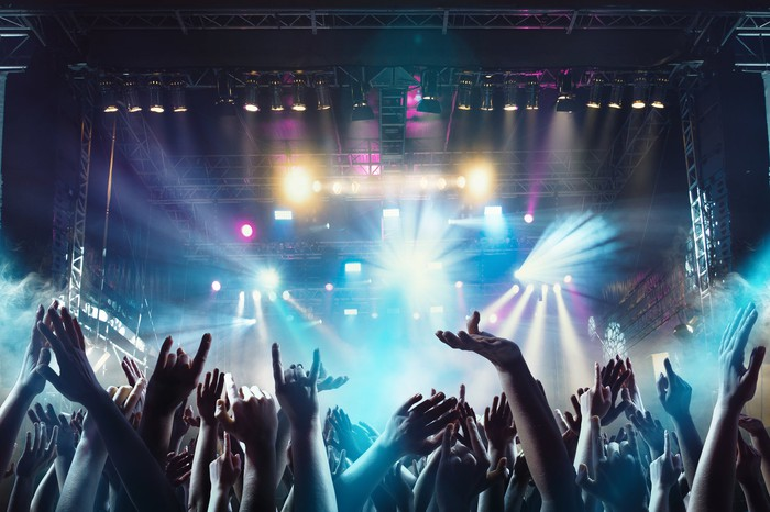 A crowd at a concert with a brightly lit stage in the background.