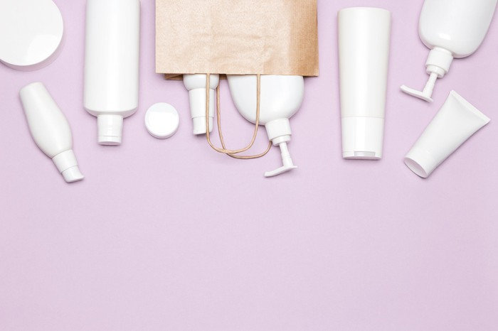 White bottles of skincare products against a pink background.