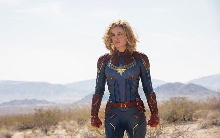 A blonde-haired woman in a red and white superhero costume standing in a dessert.