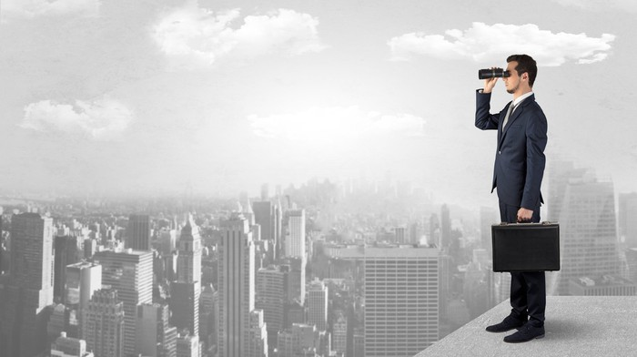 Guy in a suit standing on a rooftop and looking ahead with binoculars.