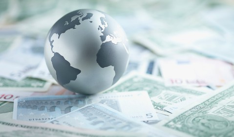 A globe sitting on top several foregin currencies.