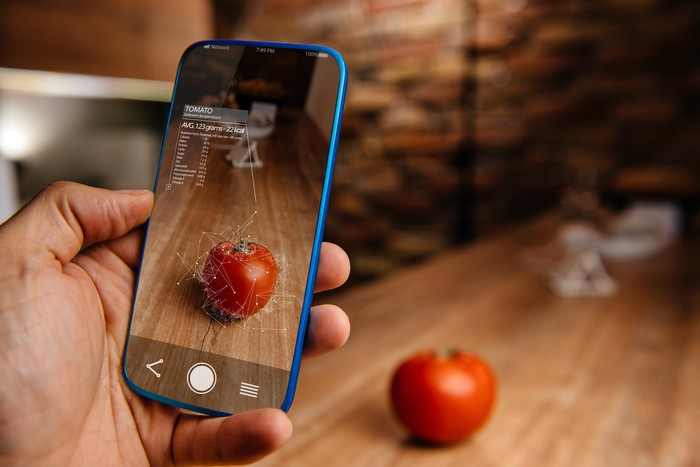 A man uses an AR smartphone app to scan an Apple.