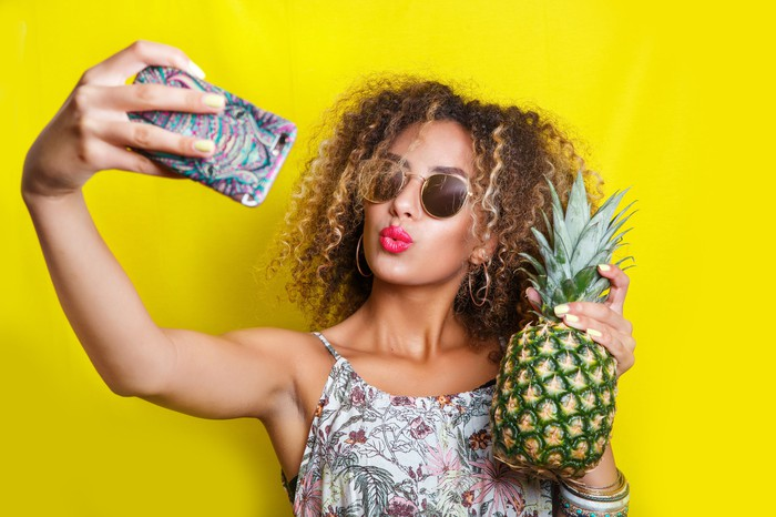 A woman takes a selfie with a pineapple
