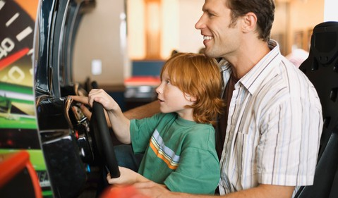 father and son playing arcade game