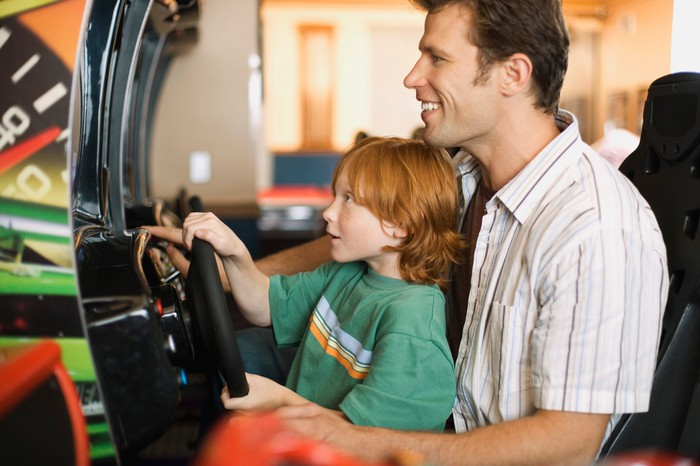 A father and son play an arcade game.