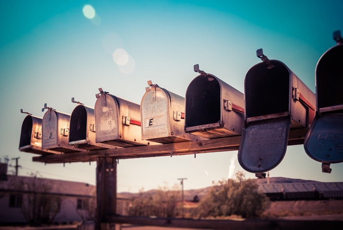 Row of mailboxes on a wood post in a rural setting.