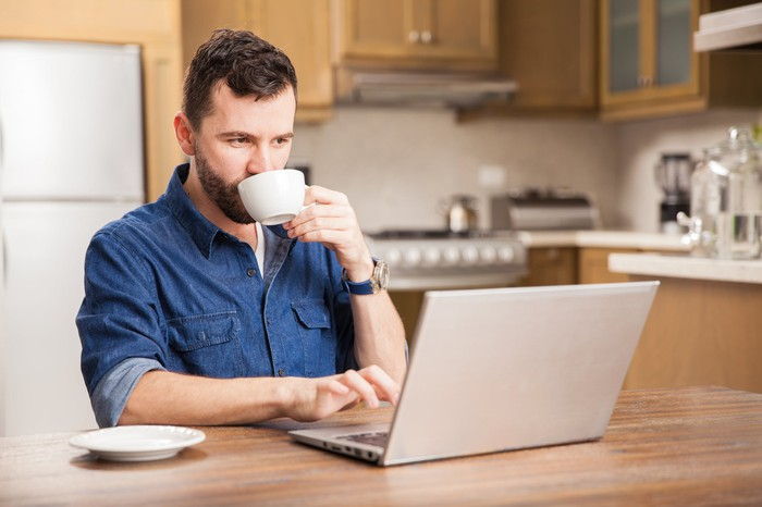 Man typing on laptop in kitchen while drinking from mug
