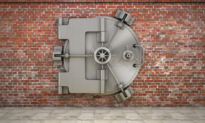 A bank vault against a brick wall.