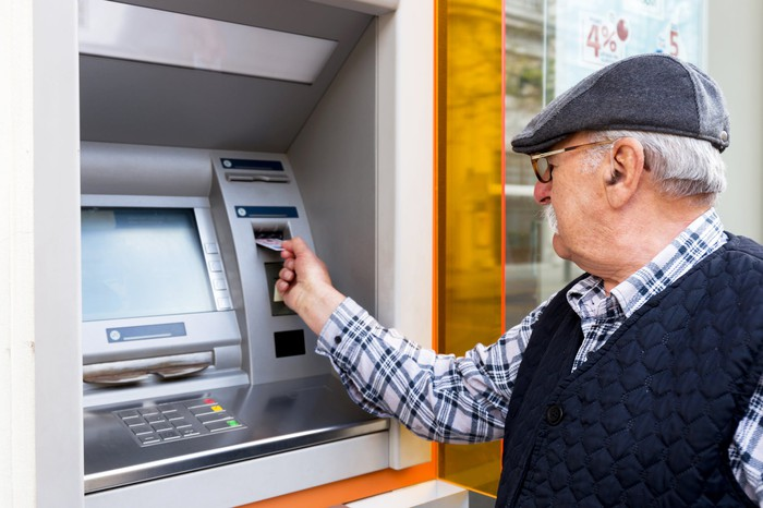 Senior man in hat inserting card into ATM