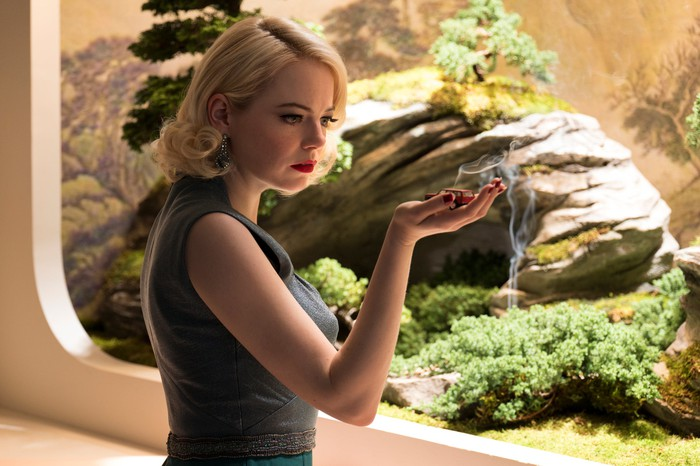 A blonde woman staring at a small toy car in her hand while standing in front of a diorama.