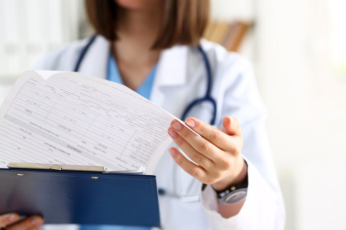 Female doctor looking at a clipboard.