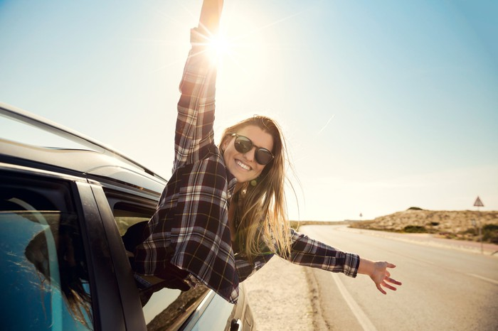 Young woman sticking body out of car window and waving hands in the air