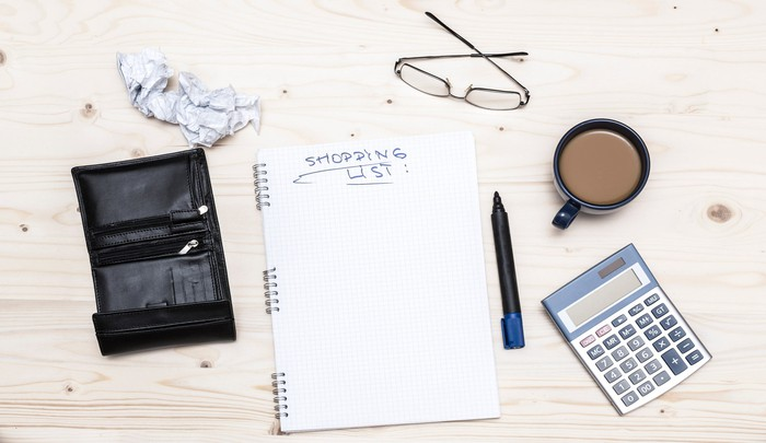 """An notebook open to a page titled """"shopping list"""" beside various desk items"""