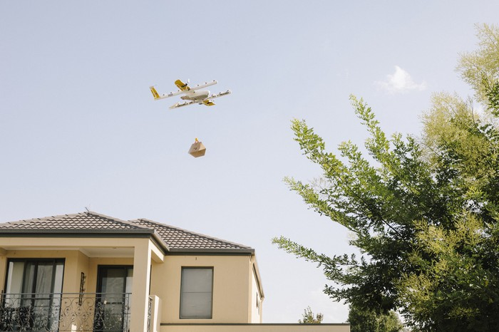 A delivery drone flying over a house