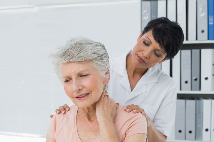 Woman in white medical coat massaging the back of an older woman rubbing her neck