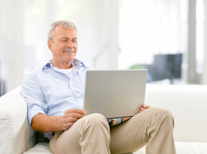 Older man sitting on couch holding laptop