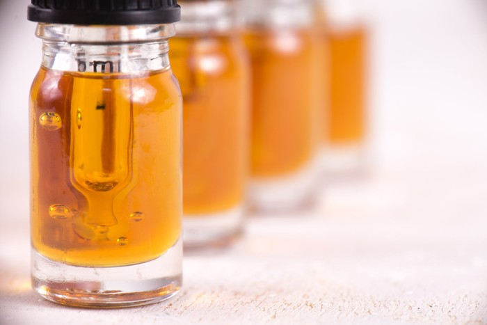 Four vials of cannabidiol oil lined up on a counter