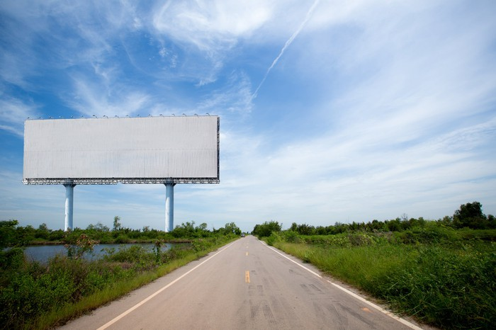 Blank billboard next to a country road