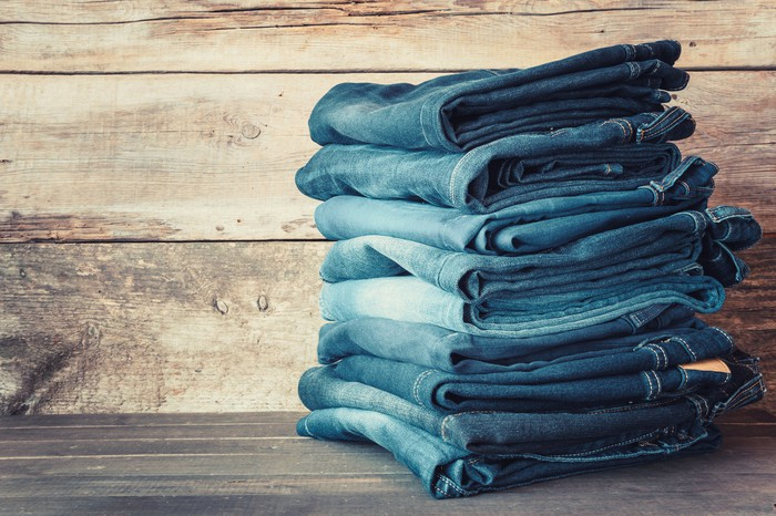 A stack of folded jeans on a wooden tabletop.