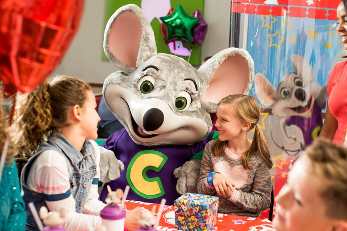 Chuck E Cheese mouse mascot with two young girls