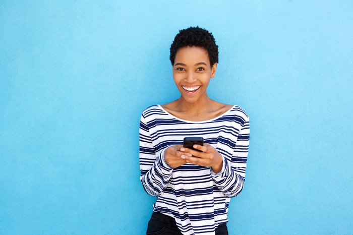 Woman smiling holding a smartphone.