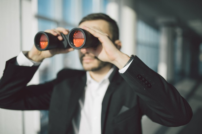 A businessman in a suit looks through binoculars.