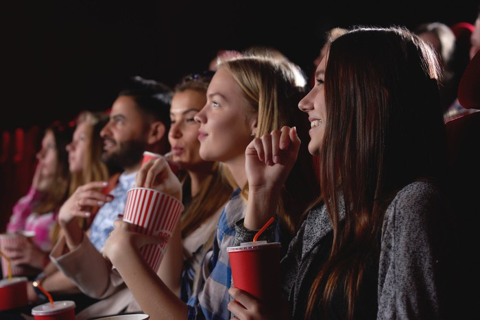 Group of friends smiling and eating popcorn in a movie theater