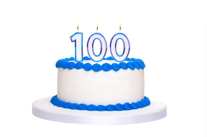 White birthday cake with blue trim and the number 100 in lit candle form on top